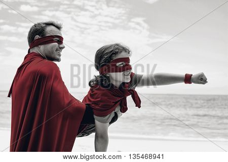 Close-up of happy father and son in superhero costume enjoying at beach