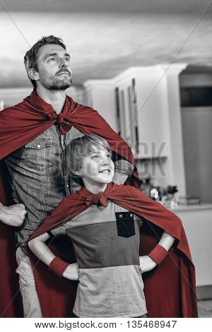 Father and son pretending to be superhero in living room at home