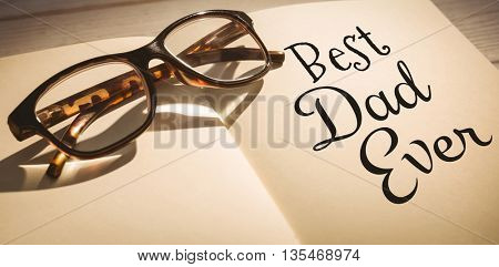 Word best dad ever on a white background against glasses on notepad
