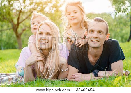 Young big happy family lying on grass in countryside