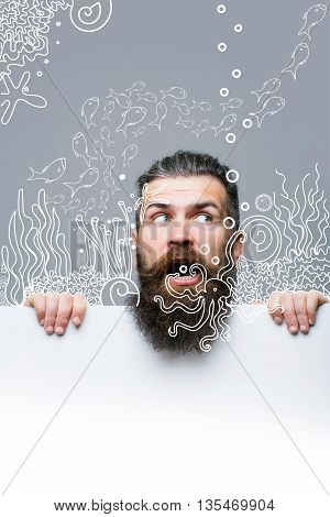 handsome bearded man with long lush beard and moustache on scared face with white paper sheet and aquarium fish on grey background copy space overlay image