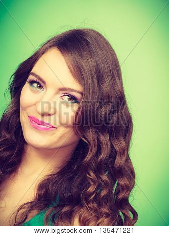 Portrait of charming woman lovely girl long curly hair make up smiling vivid color green background