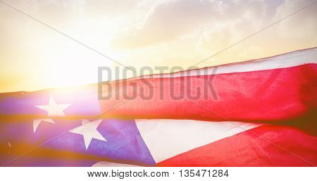 Creased US flag against sunset with clouds