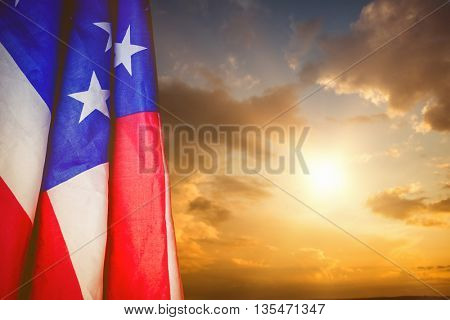 Creased US flag against blue and orange sky with clouds