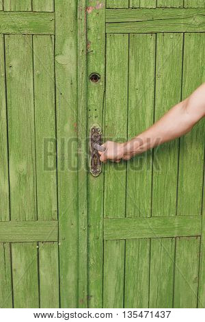 the human hand opens a closed door vintage. Green peeling paint, old wood.