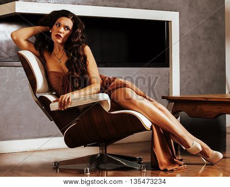 beauty young brunette woman sitting near fireplace at home, summer warm evening in interior, waiting to celebrate, people lifestyle concept