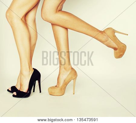 two pair of woman legs in hight heels shoes isolated on white background