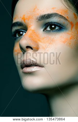 Close-up Portrait Of A Beautiful Girl With Paint Around The Eyes On A Black Background. Fashion Port