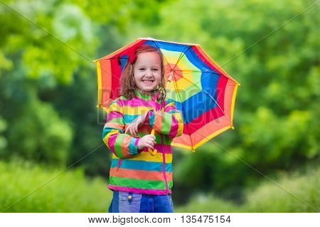 Little girl playing in rainy summer park. Child with rainbow umbrella waterproof coat and boots jumping in puddle in the rain. Kid walking in autumn shower. Outdoor fun by any weather