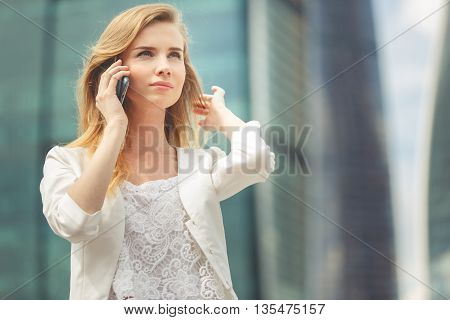 Young businesswoman talking on cellphone while walking outdoor. City business concept. Image toned in low contrast.