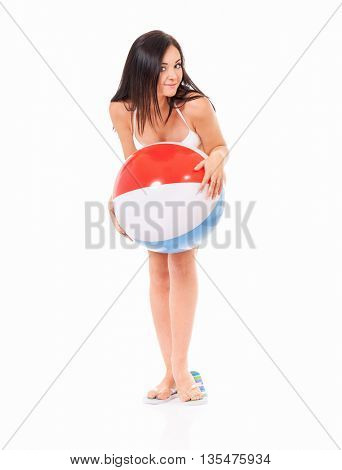 Full length portrait of happy young woman in swimsuit with beach ball, isolated on white background