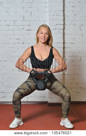 Young woman doing exercises with kettlebell at gym.