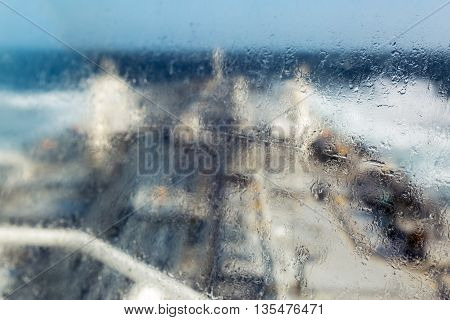 Sea drops on the ships window with blurred deck background.