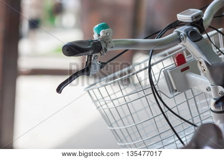 Bicycle handle with a bell and a basket closeup