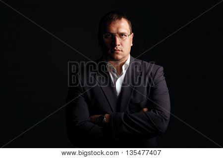 Portrait of a serious businessman on dark background