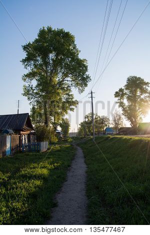 narrow road in the village going far , small country house at sunrise