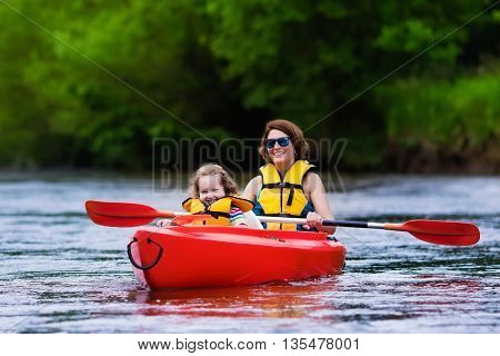 Family on kayaks and canoe tour. Mother and child paddling in kayak in a river on a sunny day. Children in summer sport camp. Active preschooler kayaking in a lake. Water fun during school vacation.