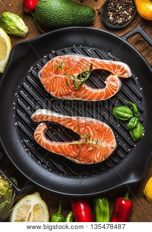 Dinner cooking ingredints. Raw uncooked salmon fish with vegetables, herbs and spices in iron grilling pan over rustic wooden background, top view