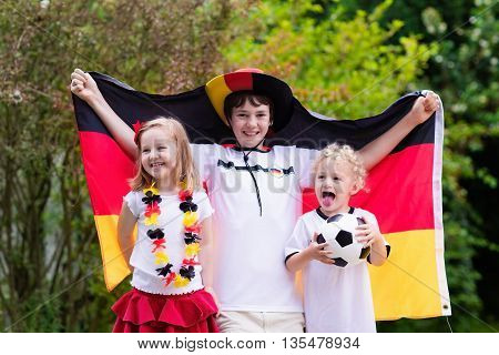 Children cheering and supporting German national football team. Kids fans and supporters of Germany during soccer championship. Family with teenager boy little girl and baby watch football game.