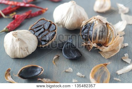 Black garlic whole and cloves scattered on white background
