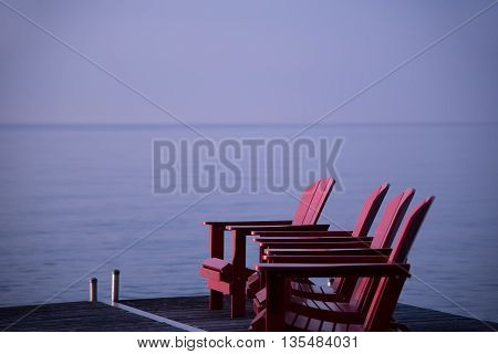 Three cottage chairs in a row on a dock at the lake