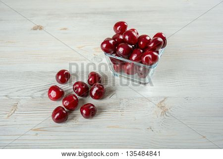 Sweet and fresh cherries in glass bowl on wooden background