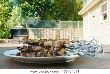 Shish kebab: slices of meat with sauce preparing on fire