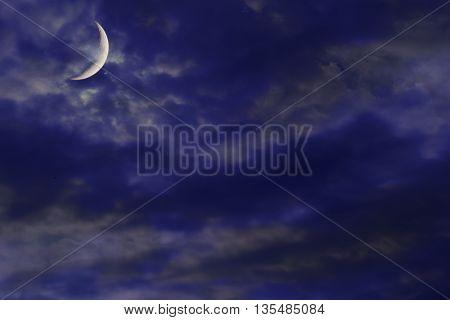 New Moon enlightens cloud in the night sky