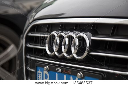 Shenzhen, China - Jun 14, 2016: Close up of the logo of Audi on the car front, taken within a test drive. Audi AG is a German automobile manufacturer that produces and distributes luxury vehicles.