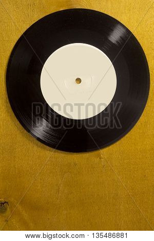 Musical vinyl record on a brown wooden background