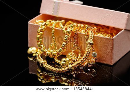 Open box with pile of various golden jewelry isolated black background.