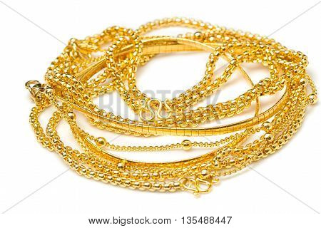 Pile of gold necklaces isolate on white background