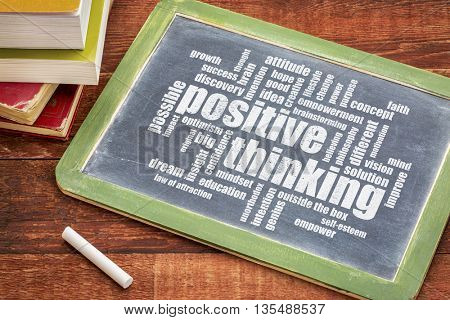 positive thinking word cloud  - white chalk text on a  slate blackboard with a stack of books against rustic wooden table