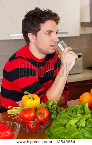 Man Drinking Orange Juice In Kitchen