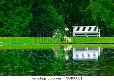 wooden bench on shore of picturesque lake