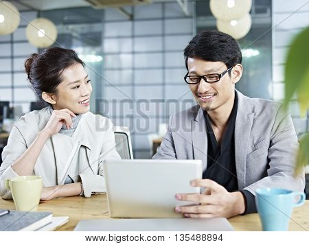 two young asian corporate people discussing business in office using tablet computer.
