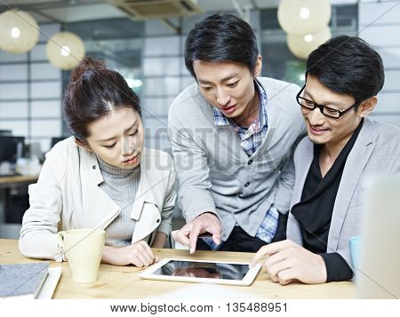 a team of young asian entrepreneurs discussing business in office using tablet computer.