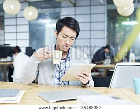 young asian business person looking at tablet while drinking coffee in office with serious facial expression.