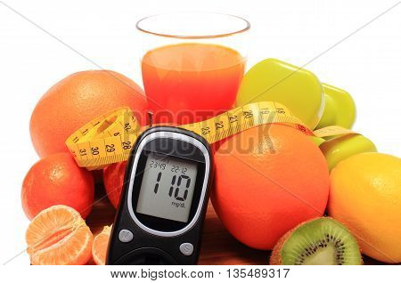Glucose meter. fresh fruits dumbbells for using in fitness tape measure and glass of juice concept for diabetes slimming healthy nutrition and strengthening immunity