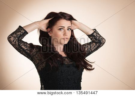 Beauty portrait of young healthy woman with hands in her hair