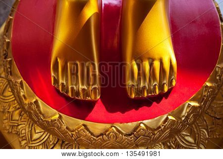 Golden feet on a red background vivid close-up. Asian shrine sculpture feet nice and clean