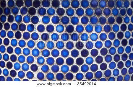 Blue penny circular ceramic tiles background. Tiled indigo color bathroom wall