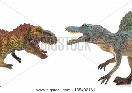 tyrannosaurus and spinosaurus toys on a white background