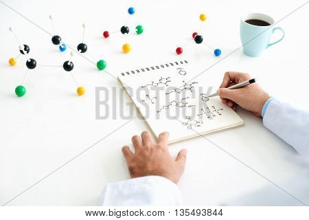 Close-up of chemist hand drawing chemical structure