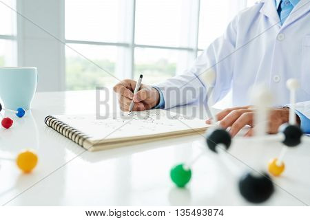 Close-up of male scientist working at the table