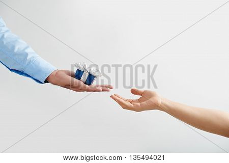 Man giving a small present to woman