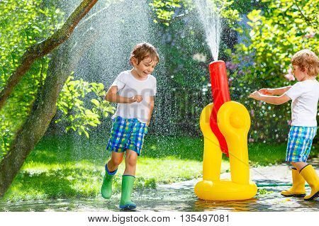 Adorable little kid boy and his brother playing together with a garden hose on hot and sunny summer day. Two siblings having fun outdoors. Funny leisure for children.