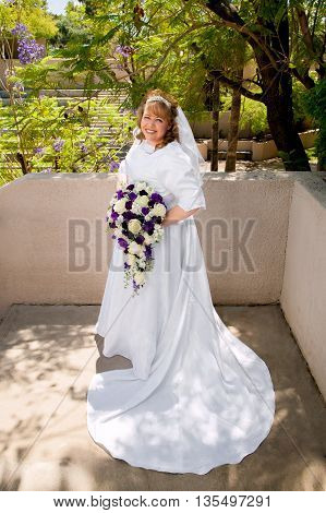 A beautiful curvy bride poses with white and purple roses.