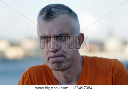 Portrait of a matured man wearing t-shirt with a troubled look on his face blurred background