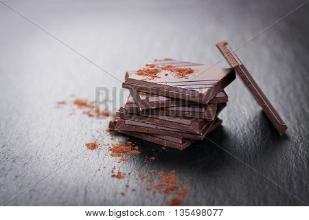 Stack of chocolate chunks on a dark stone background with cocoa closeup horizontal with copy space